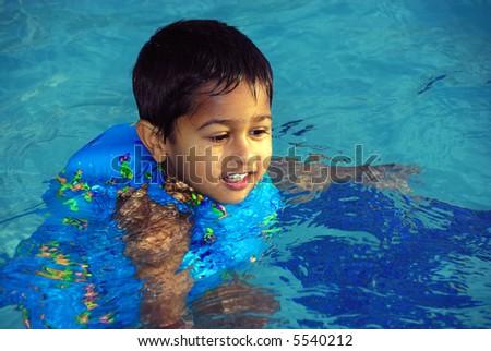 An young indian boy having fun swimming in the pool - stock photo