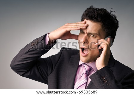 An young irritated man on phone - stock photo