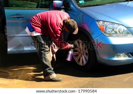 An young man washing the car wheels manually - stock photo