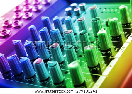 analog dj mixing console under colored disco lights - stock photo