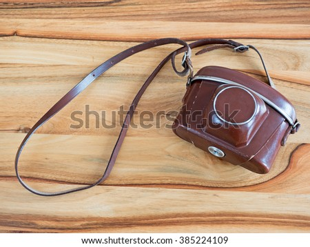 analog film camera in leather case on wooden table - stock photo