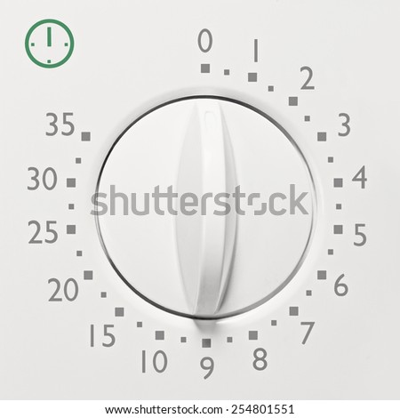 Analog 35 minute microwave oven timer, analogue vintage white dial face macro closeup, grey numbers, green icon, large background copy space horizontal - stock photo