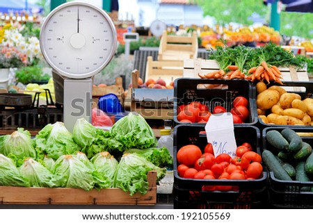 Analog scale and vegetables at farmers market - stock photo
