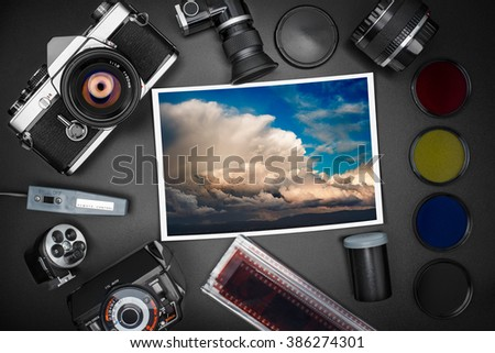 Analog SLR camera equipment around a printed photo of a cloudscape - stock photo