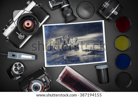 Analog SLR camera equipment around an old printed photo of a fisherman house in the sea - stock photo
