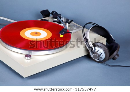 Analog Stereo Turntable Vinyl Record Player with Red Disk and Headphones - stock photo
