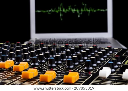 Analog studio sound mixer closeup with laptop and sound wave form in the background - stock photo