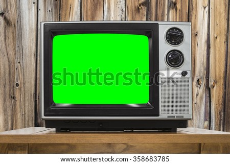 Analog television on wood wall and chroma key green screen. - stock photo