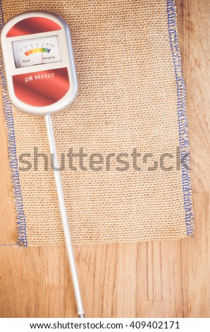 analog tool to measure soil ph on anatural wood background - copy space - stock photo