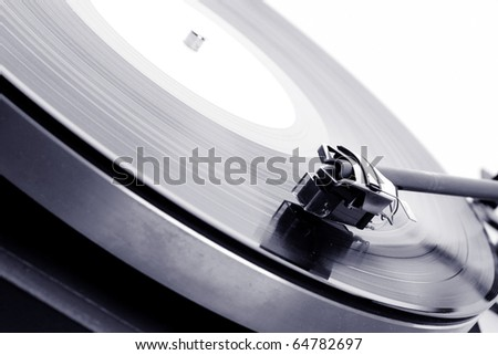Analog turntable playing record.
