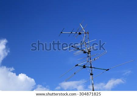 analog tv antenna with blue sky background. - stock photo