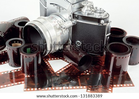 analog vintage SLR camera and color negative films on white - stock photo