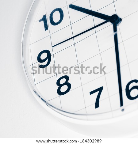 Analog wall clock, narrow focus on number nine, tinted black and white image - stock photo