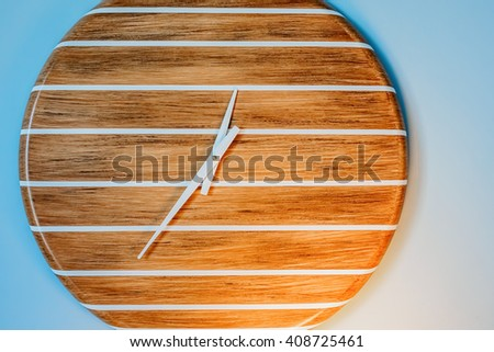 Analog wall clock with white stripes on a wooden face. No digits were used in its construction. - stock photo