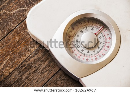 Analog weight scale isolated on wooden floor - stock photo