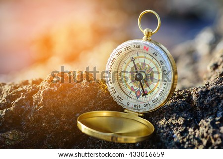Analogical compass abandoned on the rocks with blurred sea background. - stock photo