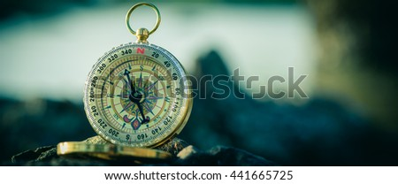Analogical compass abandoned on the rocks with blurred sea background. Vintage tone. Cinematic Style - stock photo