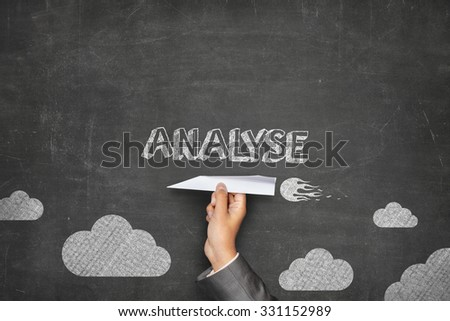 Analyse concept on black blackboard with businessman hand holding paper plane - stock photo