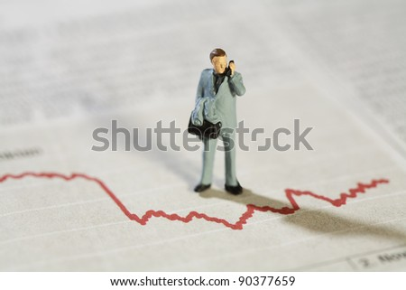 Analysing Business Statistics, a miniature model businessman stands over a red line graph talking on his mobile phone. - stock photo