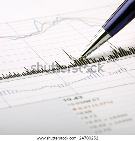 Analysis of a printed stock price chart, pointing with pen at chart feature.