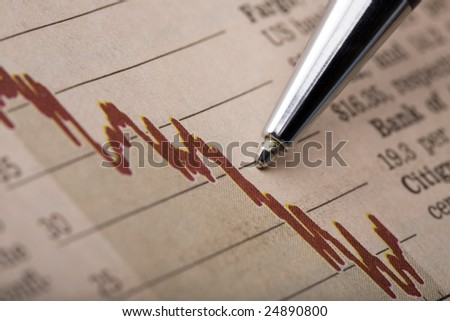 Analysis of a stock chart printed in a financial newspaper. Pen tip pointing at a declining red line graph. - stock photo