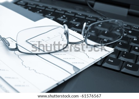 Analysis of business reports on a laptop. - stock photo
