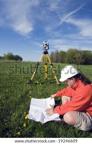 Analyzing a map - spring land surveying. - stock photo