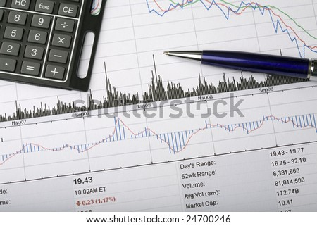 Analyzing a stock price chart, with pen and calculator - stock photo