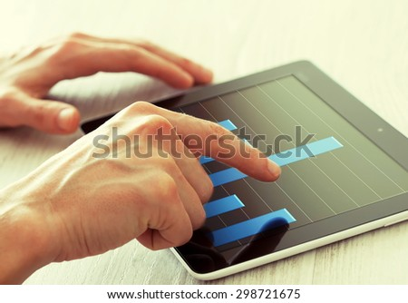 Analyzing chart on a tablet pc - stock photo
