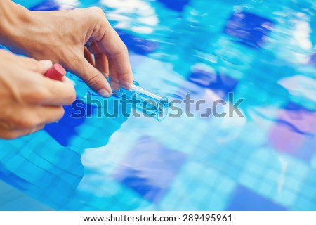 Analyzing of a water from swimming pool, taking water sample to a flask - stock photo