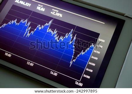 Analyzing stock market exchange with a digital tablet - stock photo