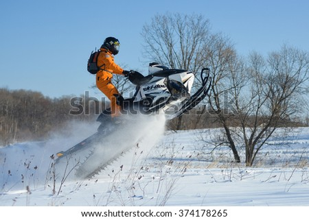 Anastasiyevka, Khabarovsk, Russian - January 18, 2015 : a man rides his snowmobile in snowy field