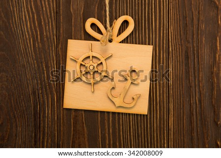 Anchor a steering wheel on an old wooden background - stock photo