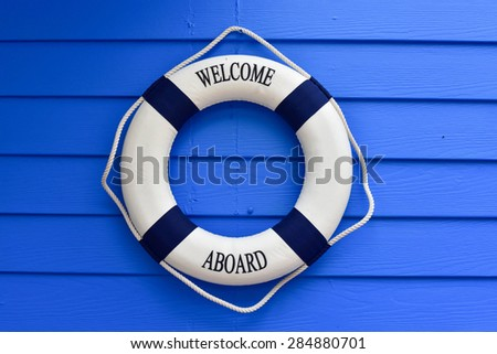 Anchor and life buoy on a background of white shabby wall boards. - stock photo