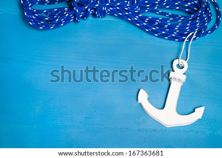 Anchor and rope on the blue wooden background - stock photo