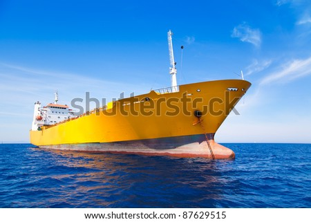 Anchor cargo yellow boat in blue sea under summer sky - stock photo