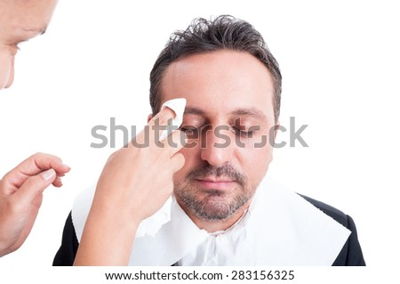 Anchor man receiving make-up before tv news - stock photo