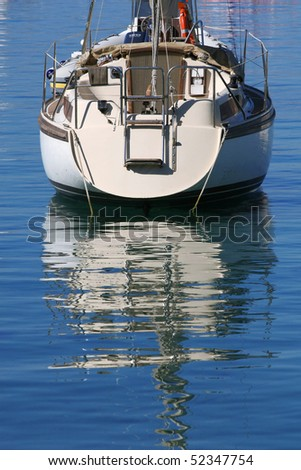 Anchored boat with a reflection - stock photo
