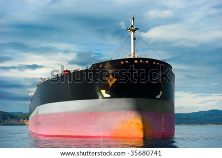 Anchored empty tanker ship under an overcast sky