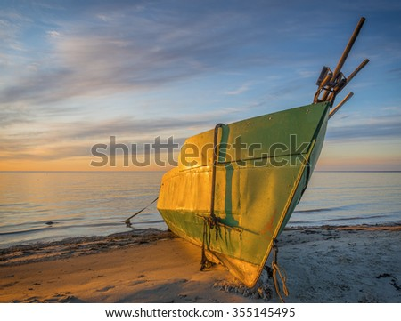 Anchored fishing boat on sandy beach of the Baltic Sea - stock photo