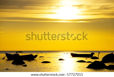 Anchored fishing boats in sunset light - stock photo