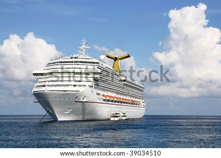 Anchored luxury cruise ship on a day with cloudy sky but calm seas. - stock photo