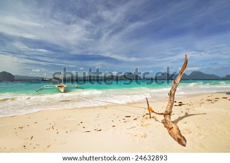 Anchored Outrigged Boat on Tropical Beach