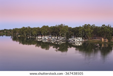 anchored residential river house boats docked on Murray river at VIC NSW border in Australia during sunrise hour - stock photo