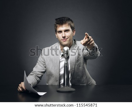 Anchorman smiling, reads the new and points the finger at the camera - stock photo