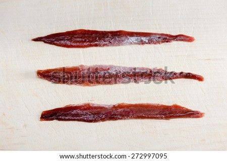 Anchovy fillets on wood - stock photo