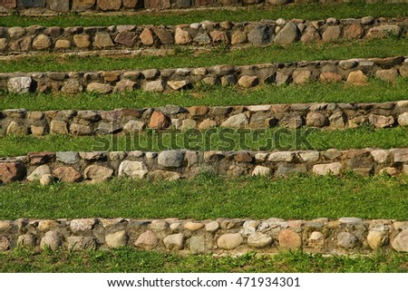 Ancient amphiteater stone stairs with green grass background