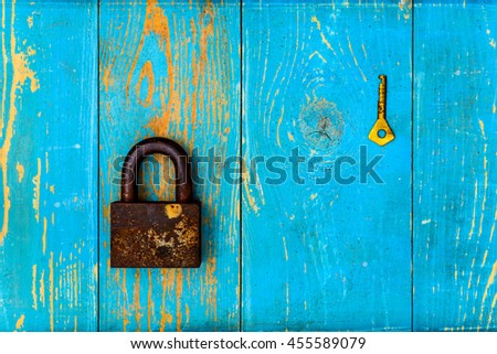 Ancient and rusty closed padlock with key on old wooden table covered with blue paint. View from above