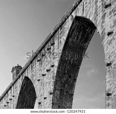 ancient aqueduct in the Lisbon built in 18th century, Portugal (black and white) - stock photo