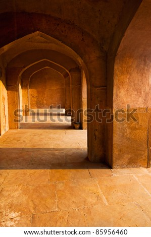 Ancient architecture. India, Delhi. Corridor with arches constructed from terracotta stones - stock photo
